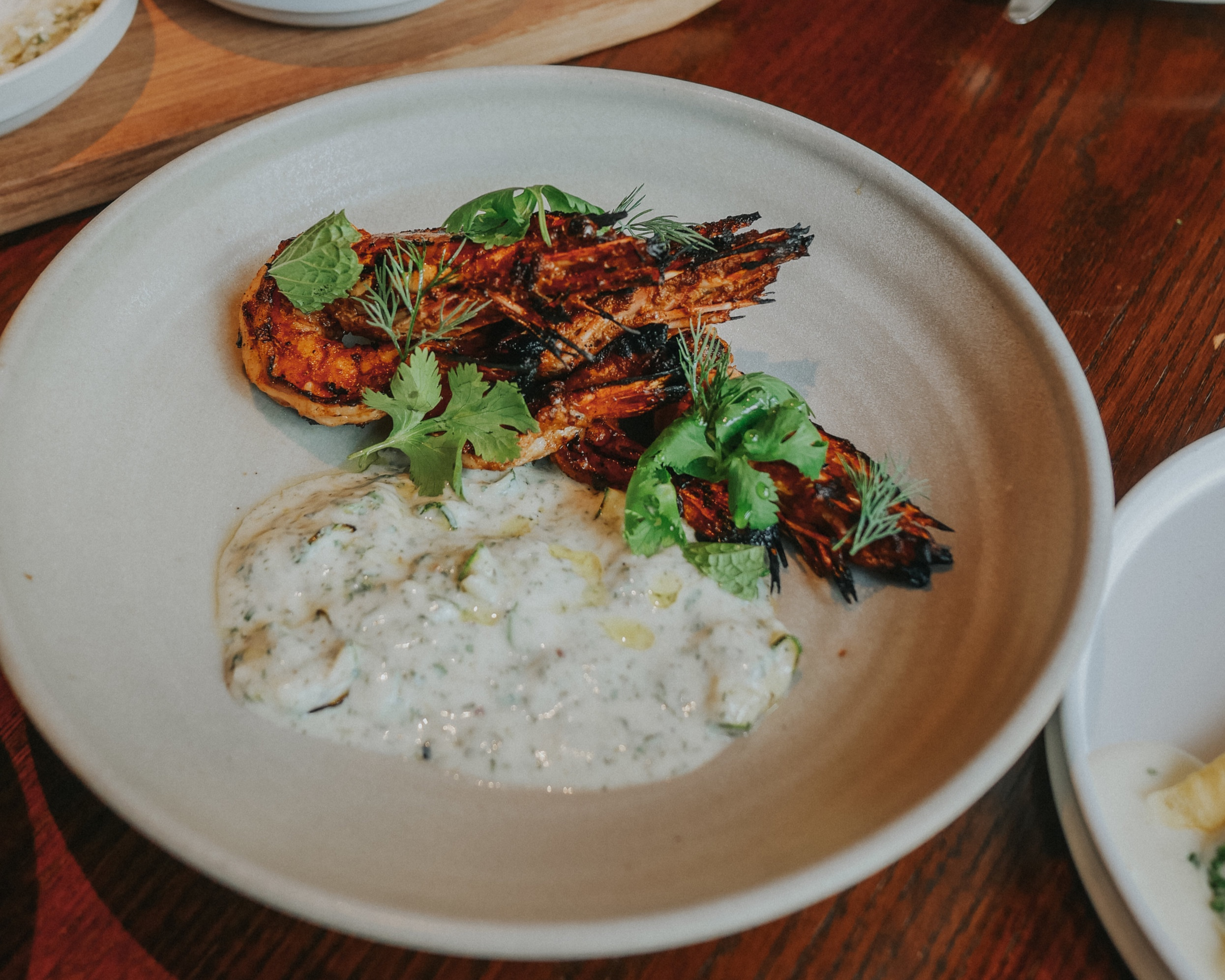 Grilled harissa marinated prawns with zucchini smoked yogurt