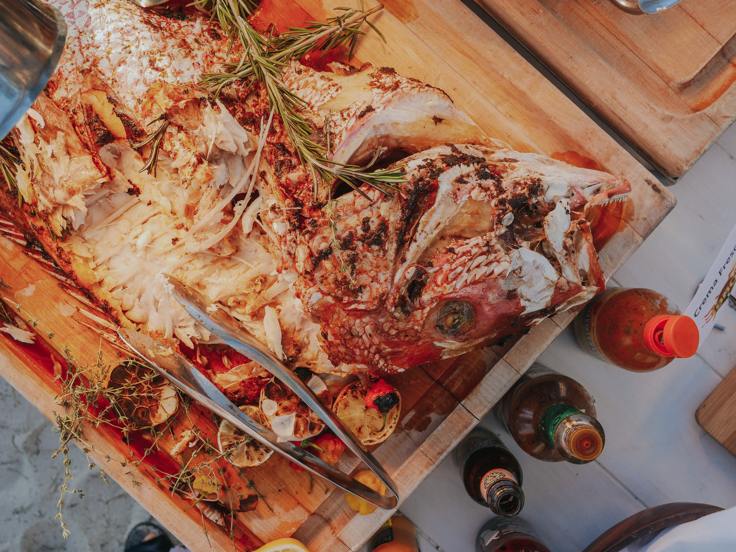 Whole grilled red snapper garnished decadently with lots of lemon, garlic and rosemary