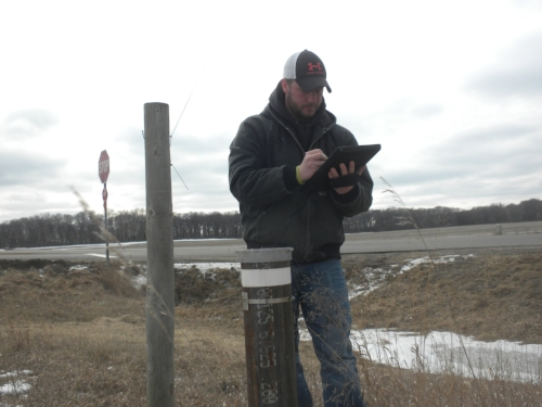 Pictured left: District Technician Nathan Sanoski, downloading data from the observation well, with a surface pro provided by the MN Department of Natural Resources.