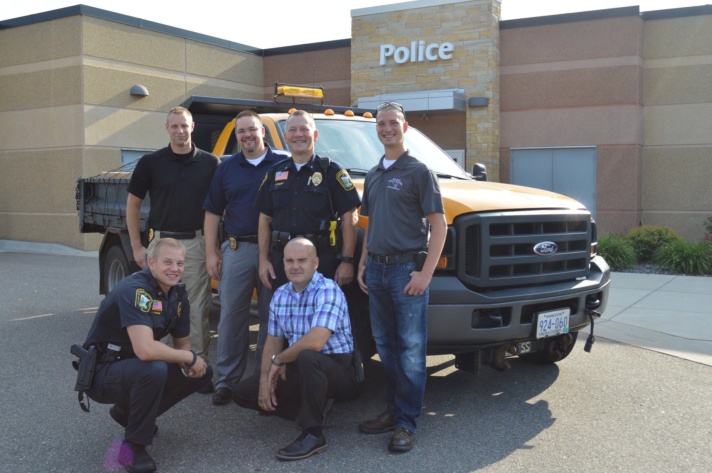 Sauk Rapids Police Officer Charles Wiggum (front, from left) and Sauk Rapids Police Detective Dan Falk; (back, from left) Sauk Rapids Police Officer Nicholas Bogart, Sauk Rapids Police Investigator Sean Gales, Sauk Rapids Police Chief Perry Beise and Benton Soil and Water Conservation District Watershed Technician Travis Janson stand in front of the Sauk Rapids Police Department Aug. 8. The officers prepared boxes of prescription medication for transport to the Pope/Douglas Solid Waste Management facility in Alexandria.    Photo Credit to Benton County News