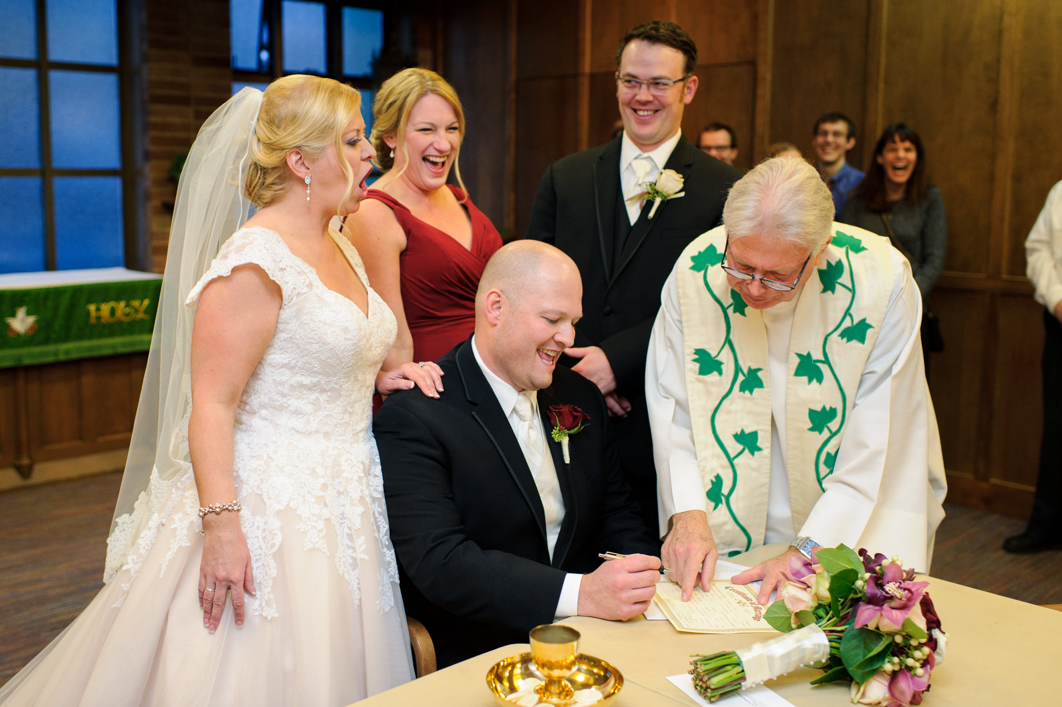 Bride and Groom and Priest Sign Marriage Certificate