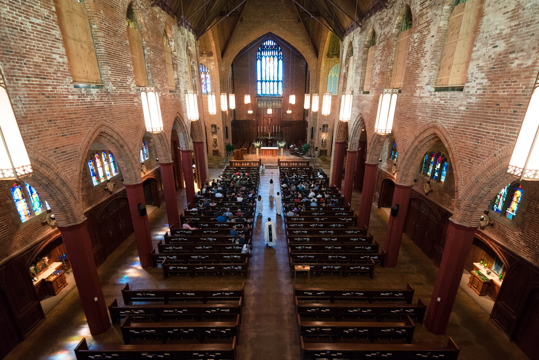 Priest Walks down Aisle during Wedding Ceremony