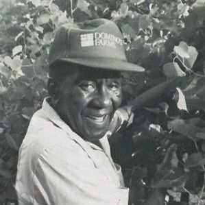 Booker T. Whatley smiling among the trees.