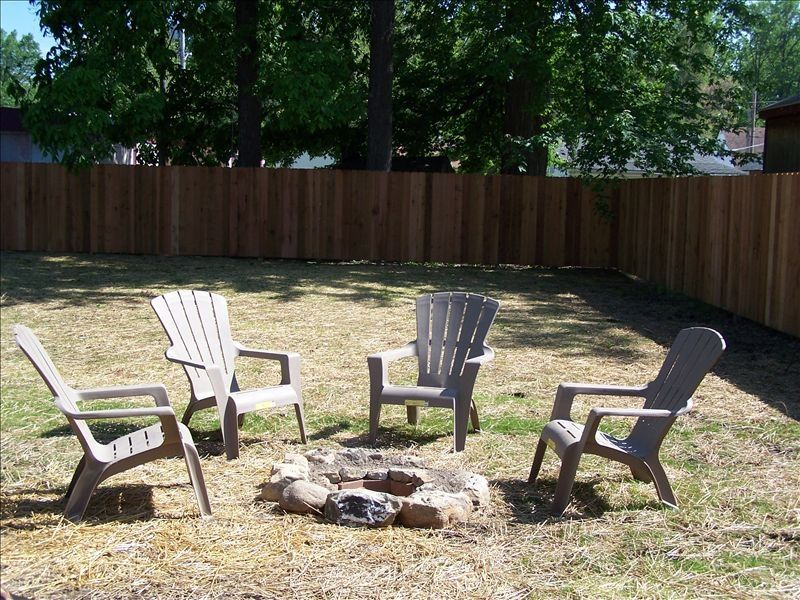 Backyard has a fire pit and charcoal grill