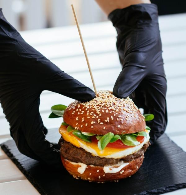hands-gloves-holding-burger