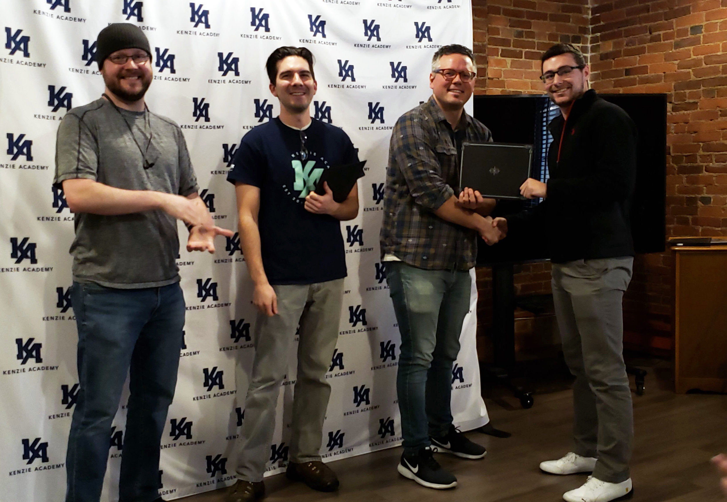 Software Engineering student, Austin Levine, accepting his Front-End Web Development Certificate from Matt, Taylor & DMG
