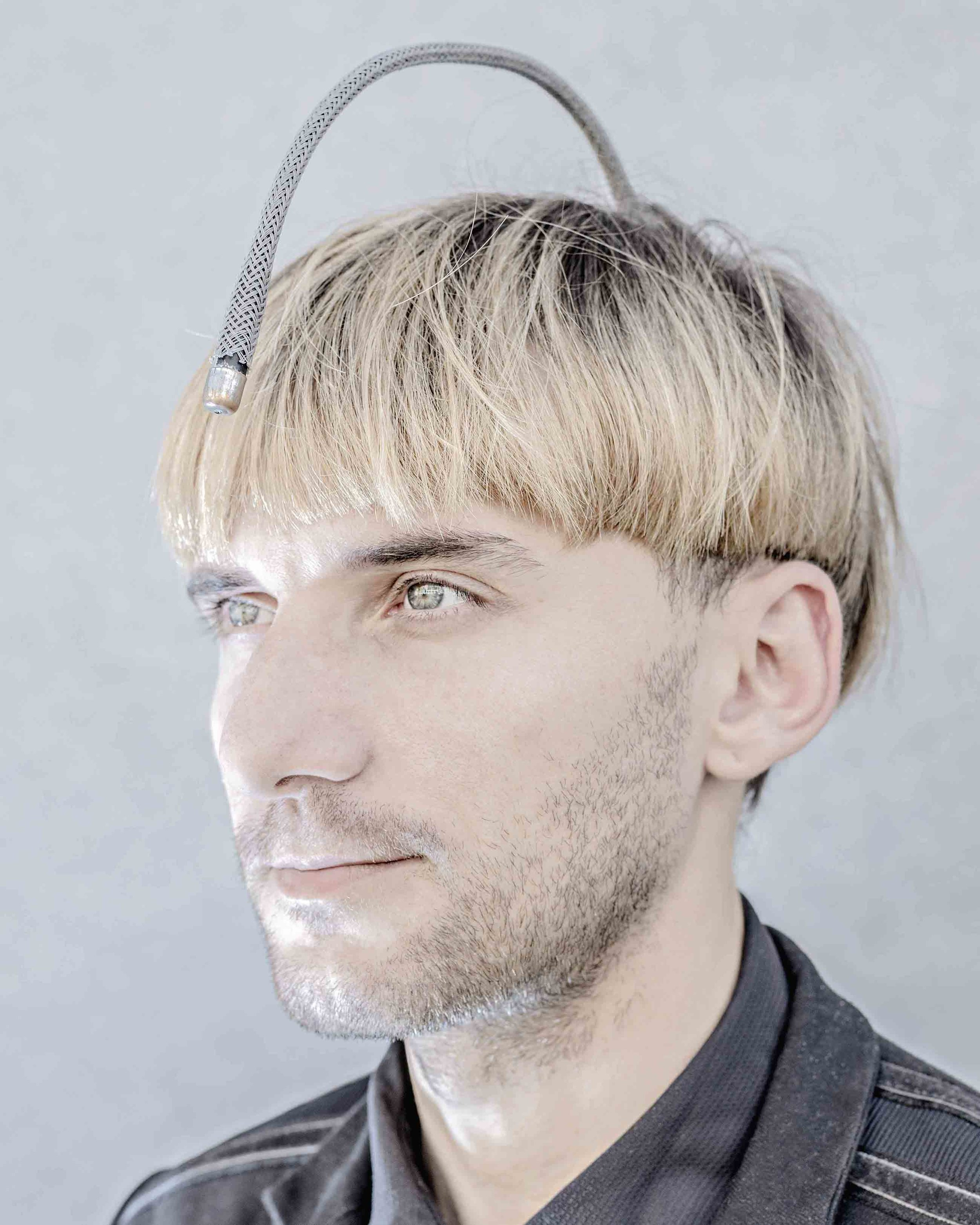 Matthieu Gafsou.  Neil Harbisson considers himself a cyborg. Suffering from achromatopsy, a rare form of color blindness, he had a prosthesis called Eyeborg implanted into his skull that senses colors and converts them into sound waves. Harbisson pleads for the enhancement of human creativity and sometimes distances himself from transhumanism, deeming it too stuck in stereotyped or commercial representations. His vision is more that of an artist than a disciple of technoscience. He takes pride in being the first human to appear with his prosthesis on his passport photo.  Munich, July 15, 2015.  Courtesy of the artist, Galerie C and MAPS.