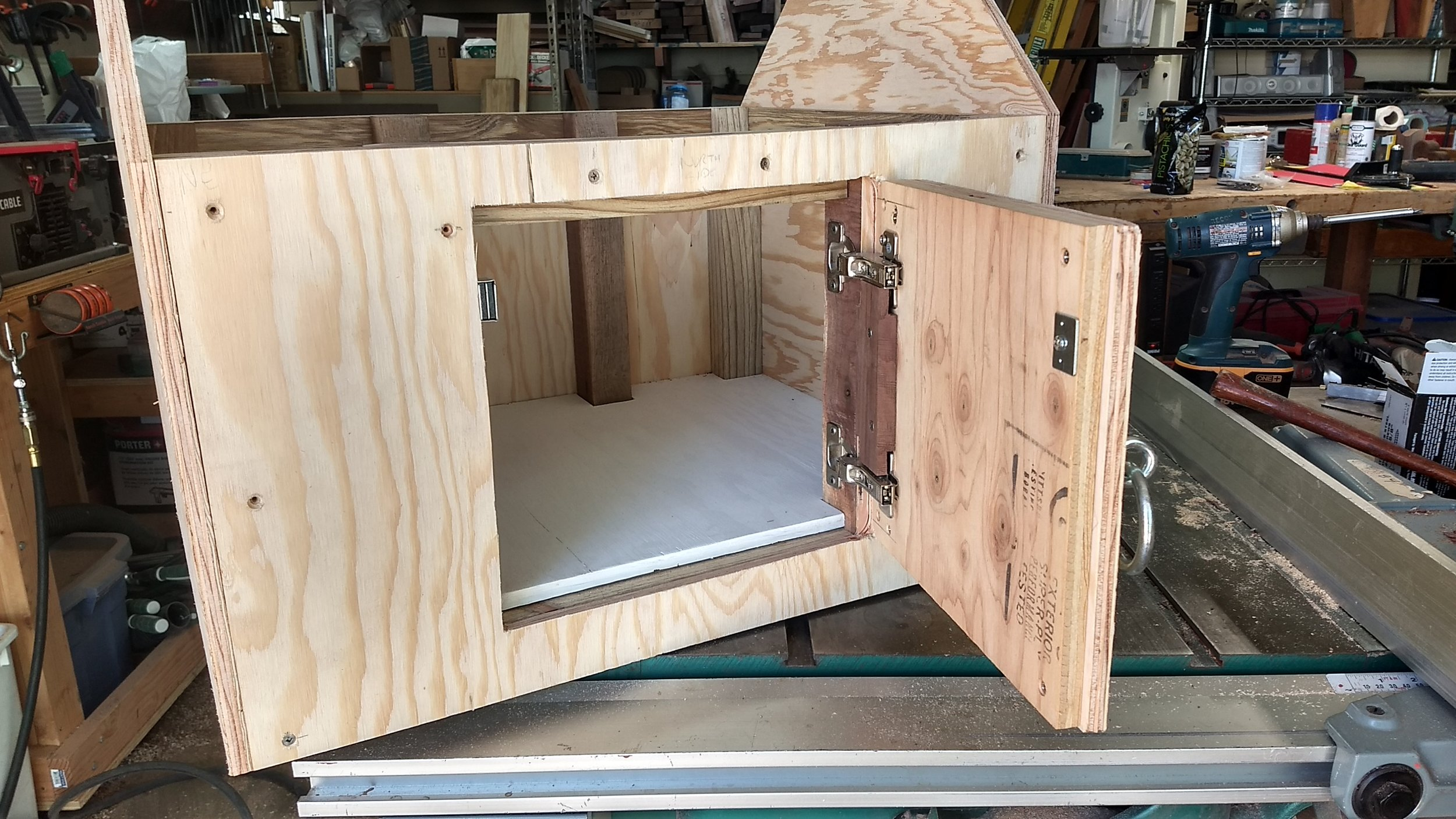 A hole for the door was cut into the plywood on front side. The door is tempoprarily attached with a all hardware installed.