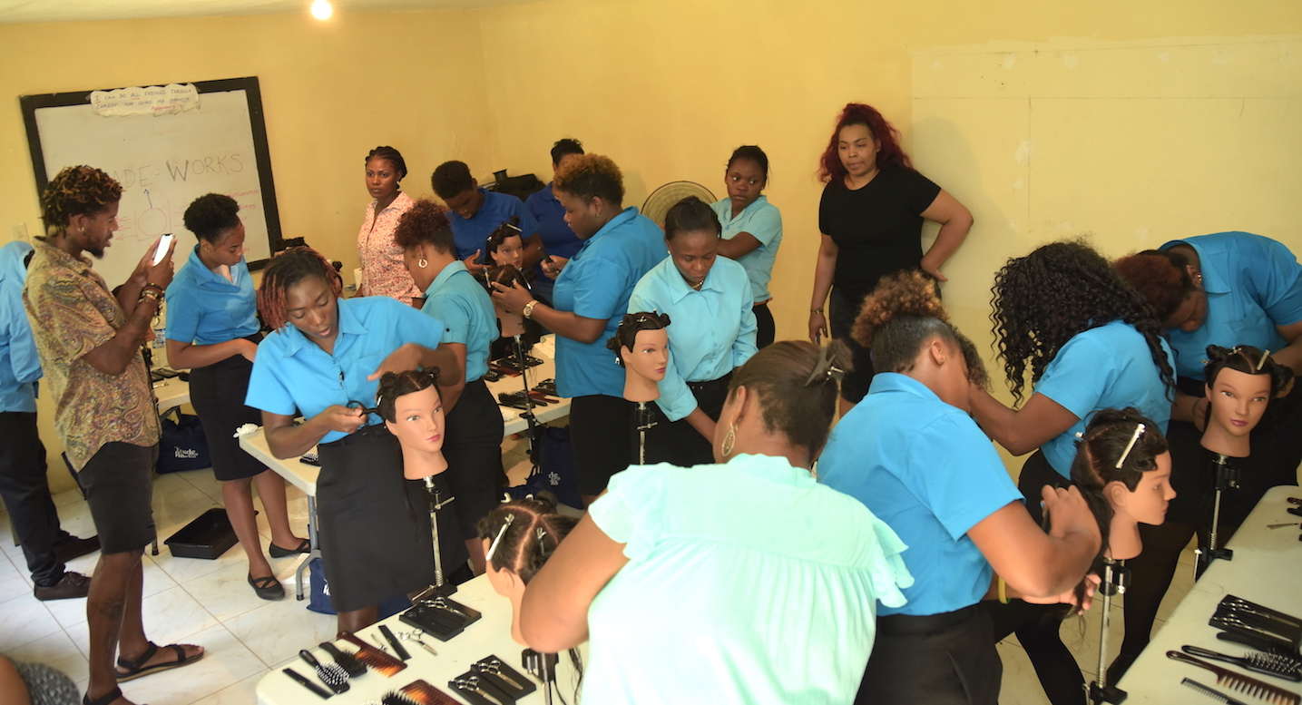 Youths in Jamaica learning cosmetology skills from Trade Works teachers