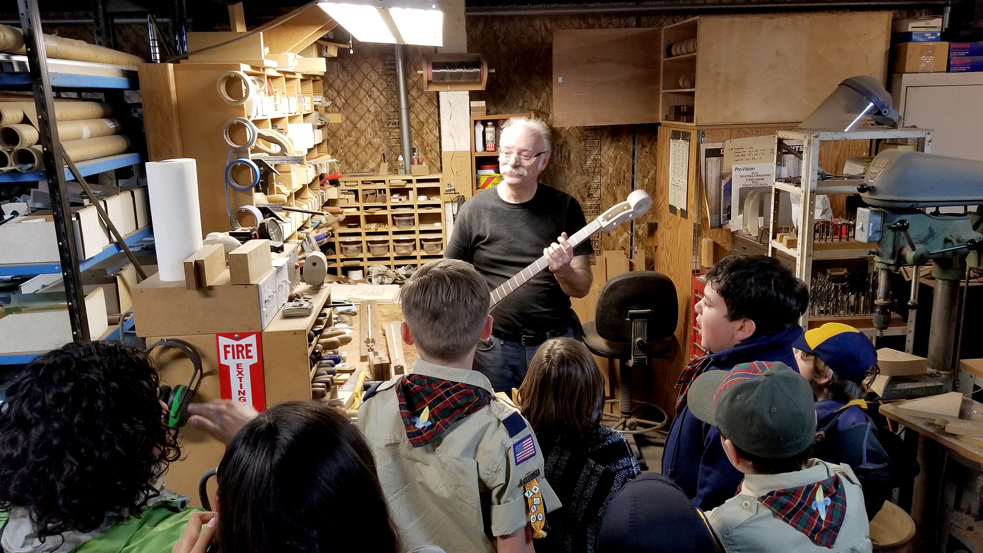 (above) Boy Scouts learning from Bruce Johnson, one of several luthiers (guitar makers) at the Packinghouse Creative, teaching scouts about how he uses each tool in the guitar making process.
