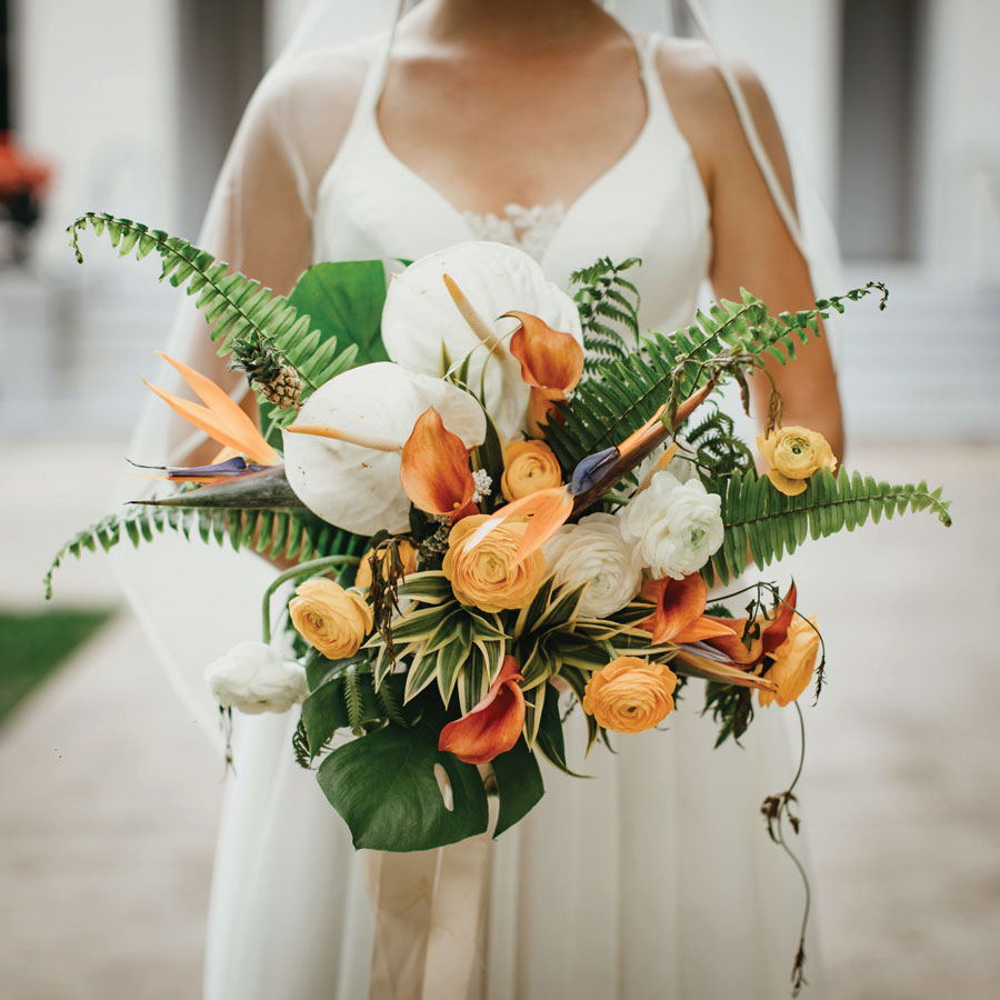 Bride Carley showing off the beautiful orange calla lilies in her bouquet. The Edwards-Beckner Wedding, page 43 of bridebook 2019. Image by Pat Cori Photography.
