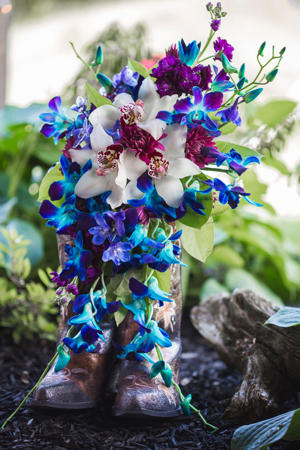 Bri Swarm chose stunning blue orchids to match with her palette as well as the color smoke bombs they used for photos. Eades-Swarm Wedding, page 66 of bridebook 2019. Image by Olivia Diane Photography.