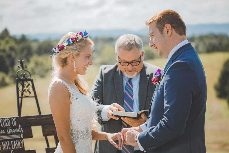 Bride Bri smiles at husband Matthew as they exchange vows and rings during their July wedding ceremony. Eades-Swarm Wedding, page 66 of bridebook 2019. Image by Olivia Diane Photography.