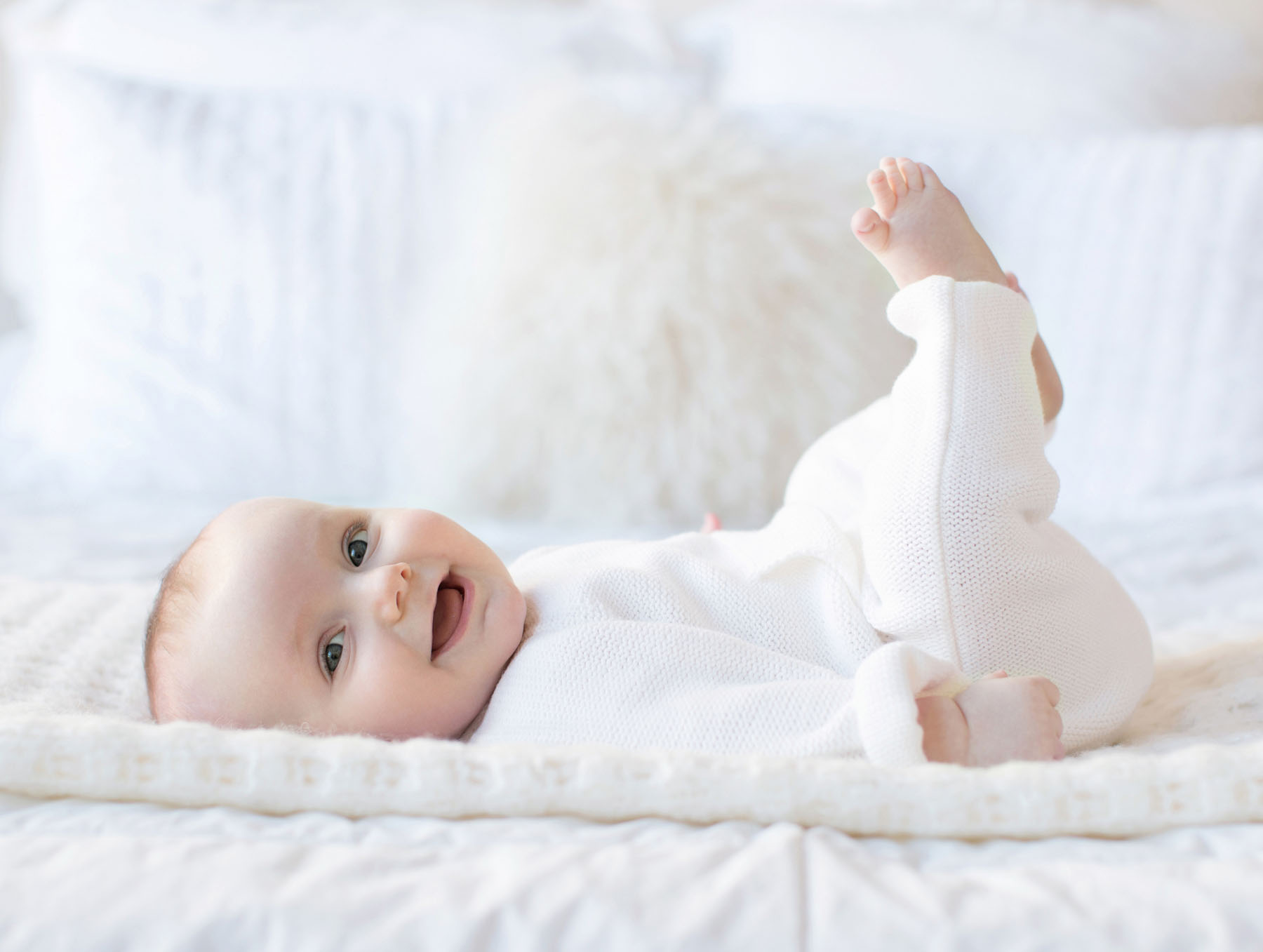smiley_baby_in_white_on_bed_six_months.jpg