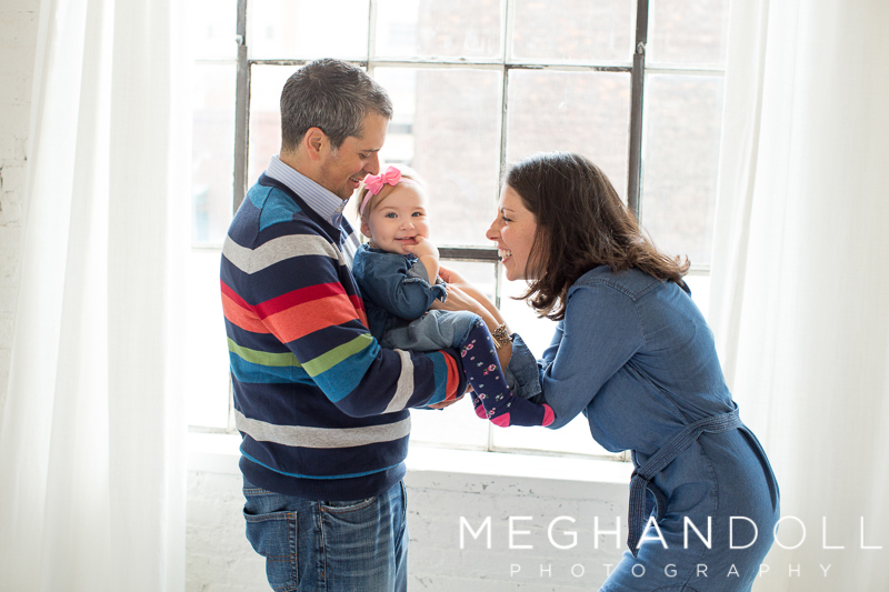 one-year-old-girl-in-denim-plays-with-parents