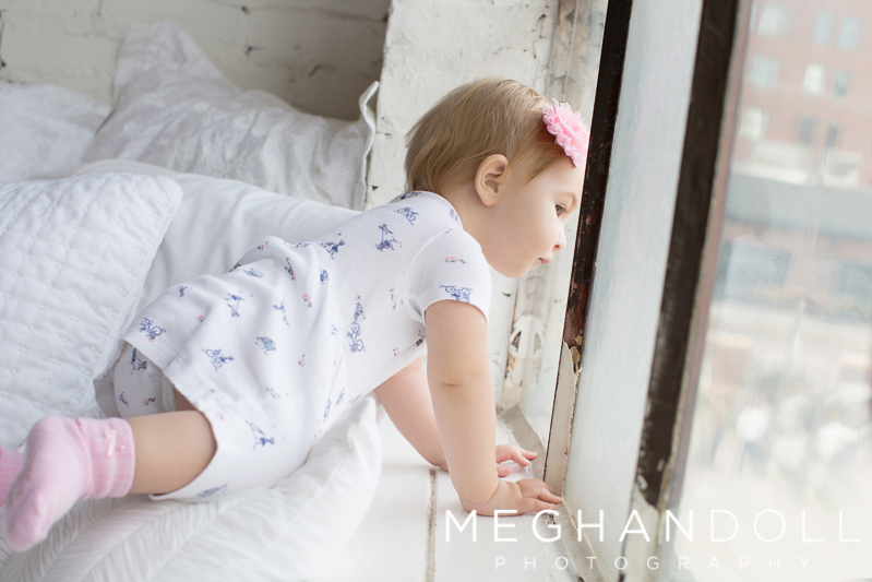 one-year-old-girl-on-bed-looks-out-the-window