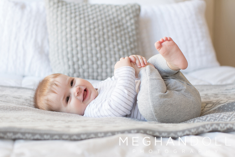 silly-six-month-old-boy-plays-with-his-toes-on-bed