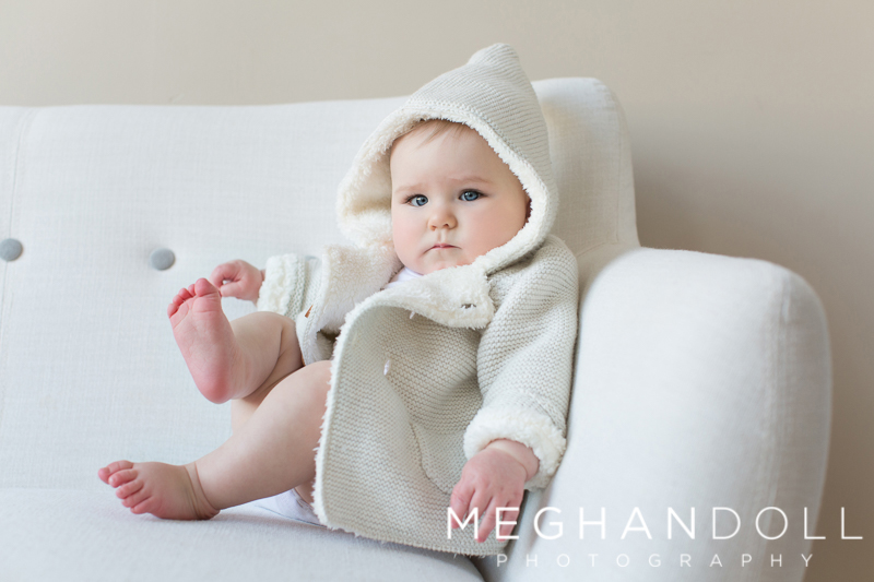 serious-little-six-month-old-boy-holds-his-toe