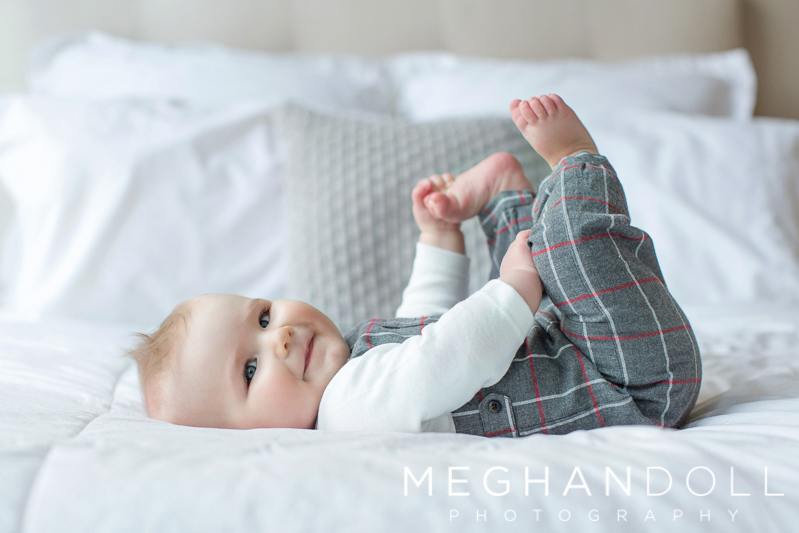 six-month-old-boy-plays-with-his-toes-on-bed