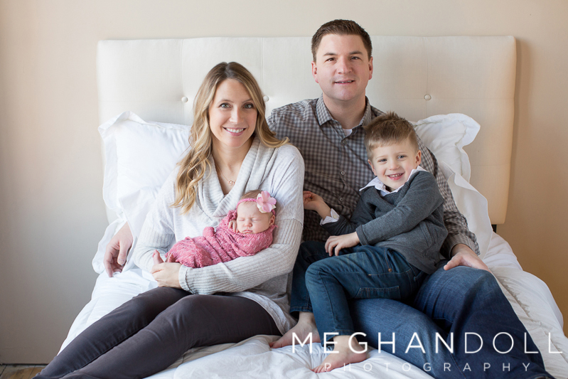 family-of-four-snuggles-new-baby-girl-on-bed