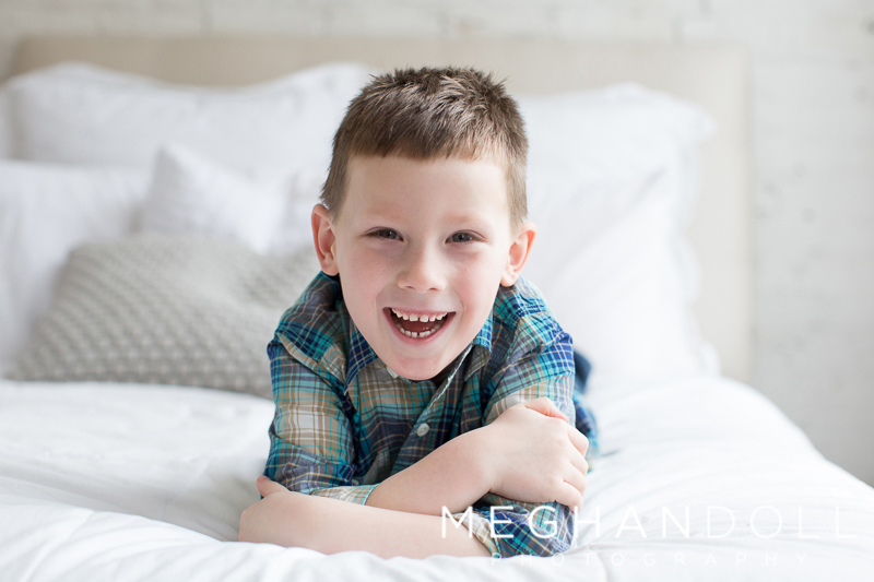 little-five-year-old-boy-smiles-on-bed