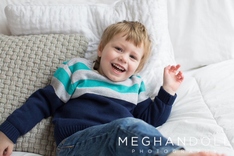 smiley-three-year-old-boy-falls-onto-pillows