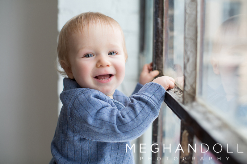 one-year-old-boy-smiles-by-window