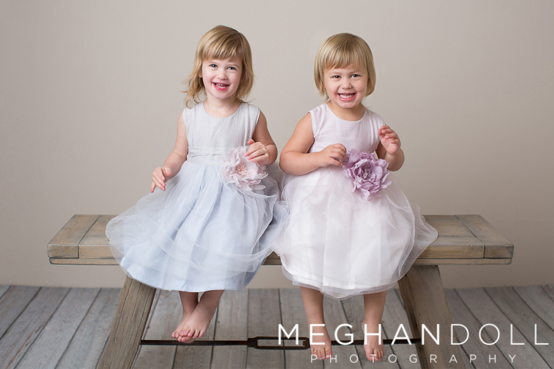 twin-girls-in-matching-dresses-laugh-on-bench
