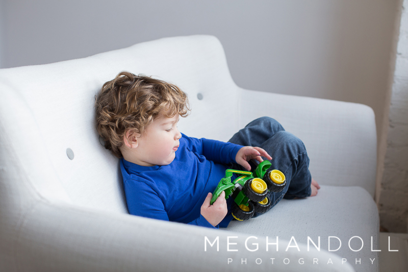 sweet-two-year-old-boy-plays-with-truck-on-couch
