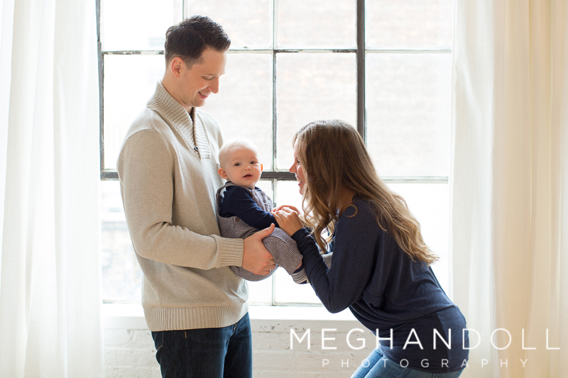 mom-and-dad-play-with-6month-old-baby-boy-by-window
