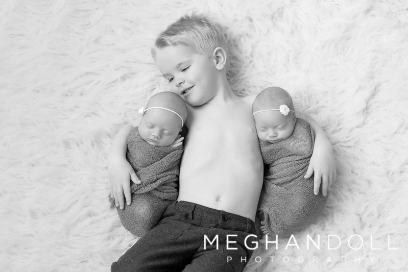 big-brother-holds-twin-sisters-on-floor