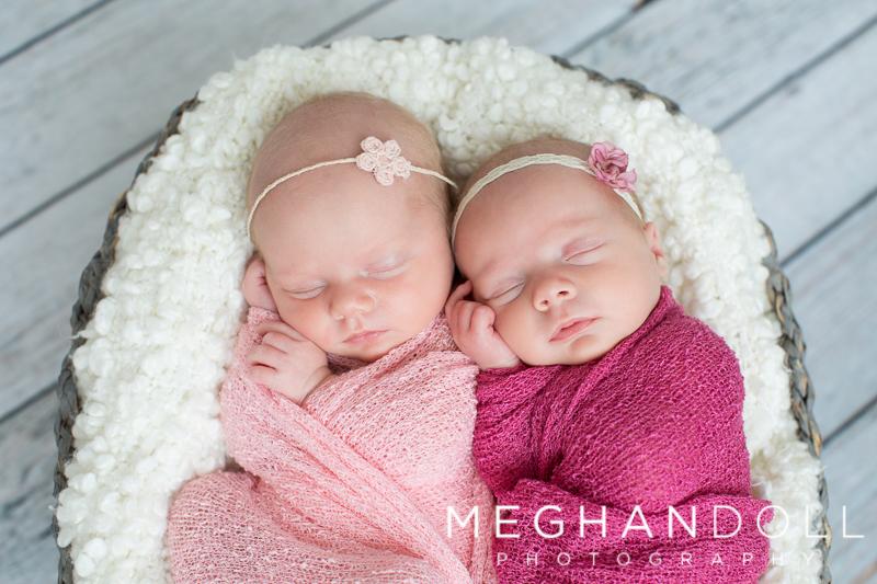 twin-newborn-girls-snuggle-in-basket-in-pink