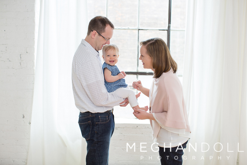 mom-and-dad-play-with-one-year-old-girl-by-window