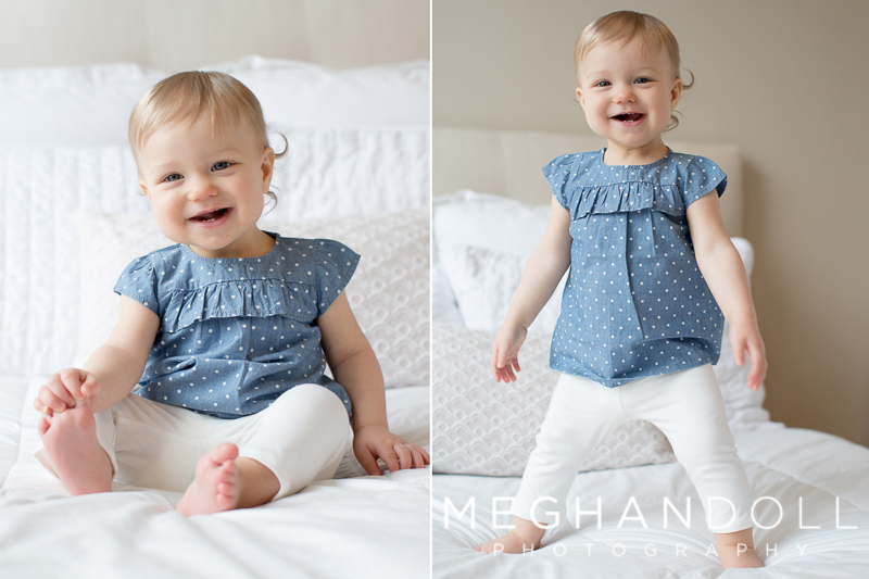 one-year-old-girl-in-blue-plays-on-bed
