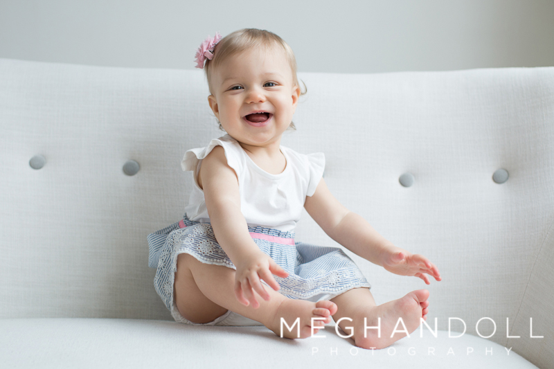 sweet-one-year-old-girl-plays-on-button-couch