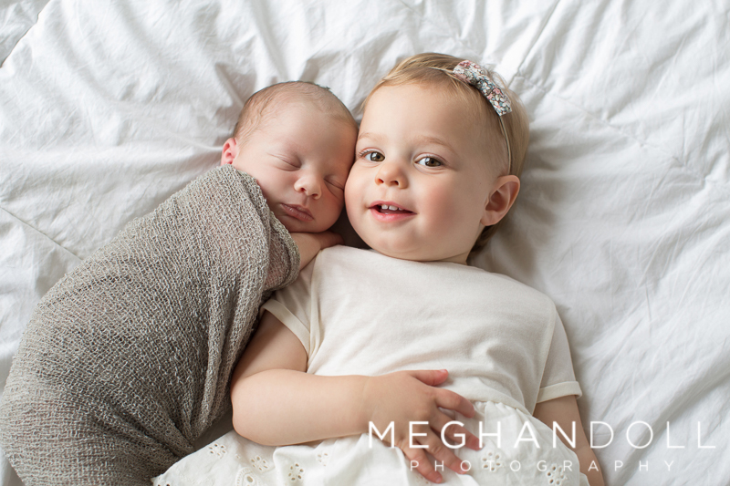 big-sister-lays-with-newborn-brother-on-bed