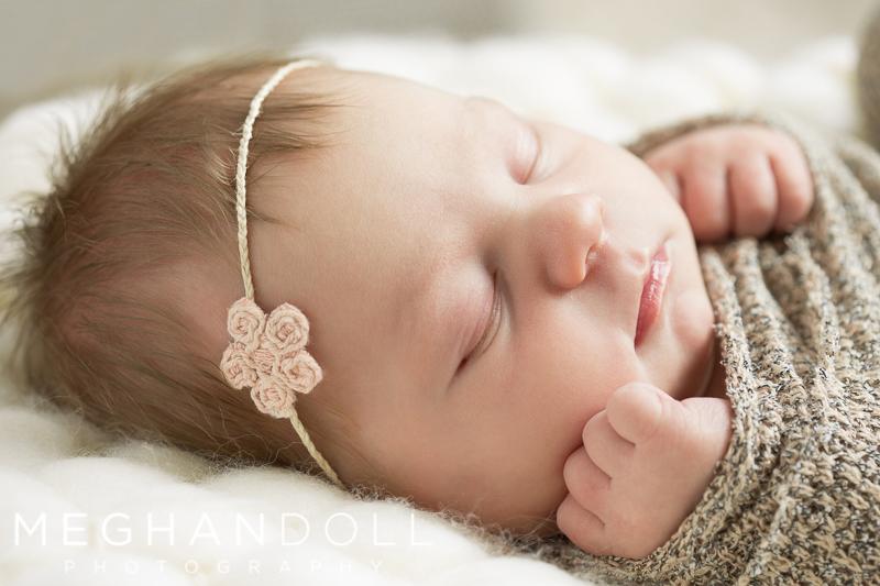 newborn-baby-snuggled-with-pink-flower-headband