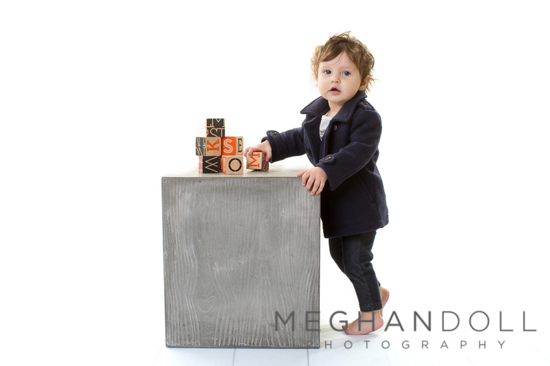 one-year-old-in-peacoat-plays-with-blocks