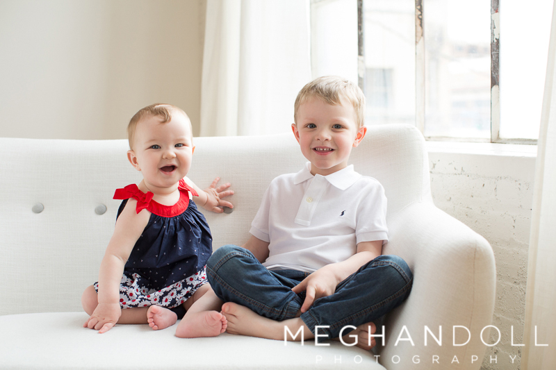 brother-and-sister-in-navy-smile-on-couch