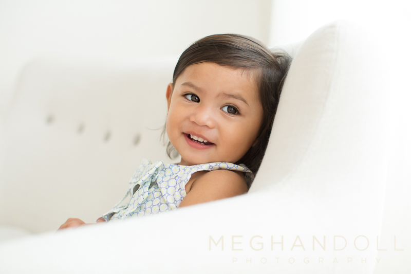 sweet-toddler-girl-smiles-over-her-shoulder