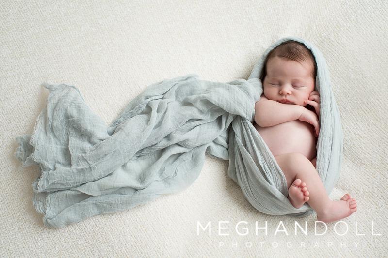 chubby-newborn-boy-sleeps-wrapped-in-light-blue