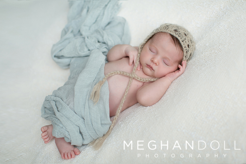 sleepy-newborn-boy-in-light-blue-and-tan-hat