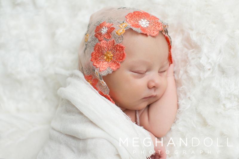 newborn-girl-in-flower-bonnet-sleeps-on-white-blanket
