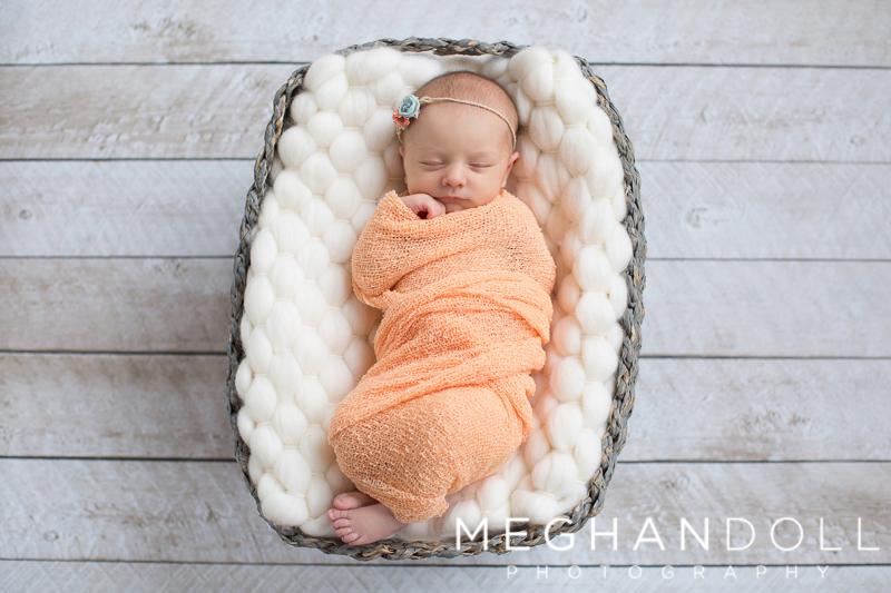 newborn-girl-in-orange-sleeps-in-gray-basket