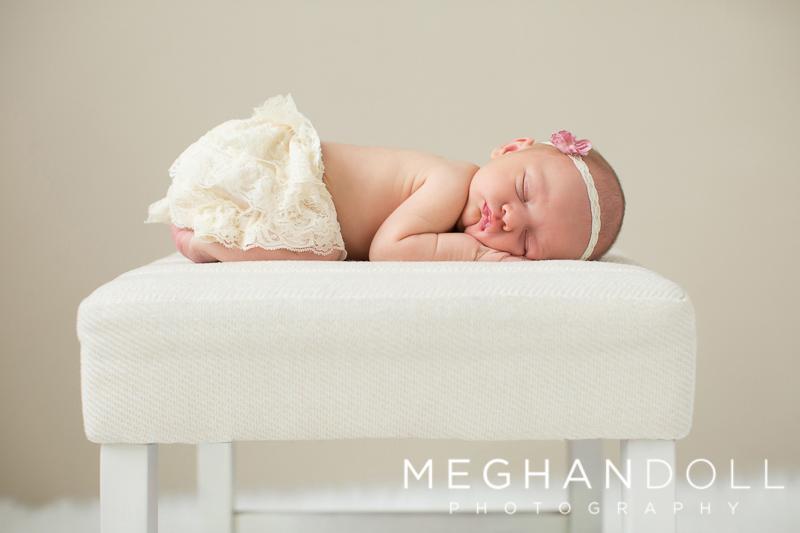 newborn-girl-sleeps-on-white-stool