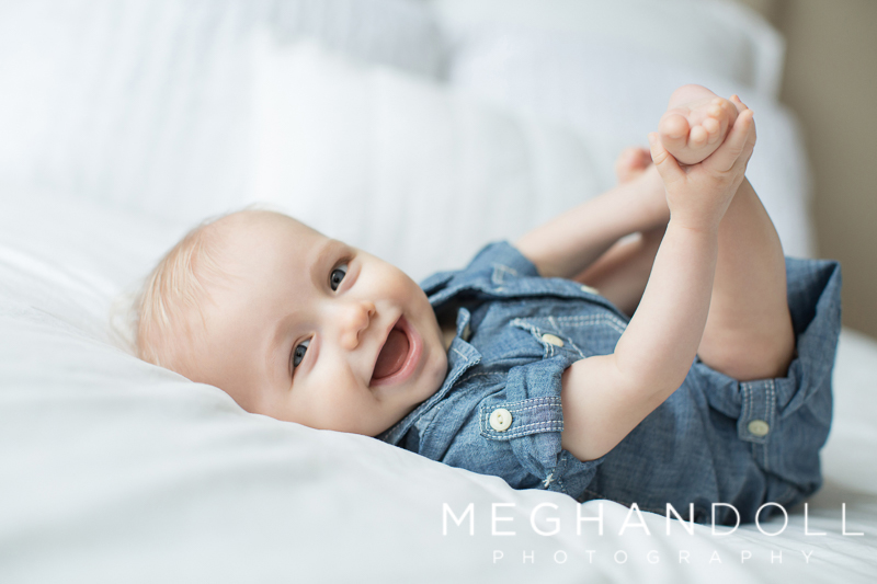 six-month-old-in-denim-plays-with-his-toes