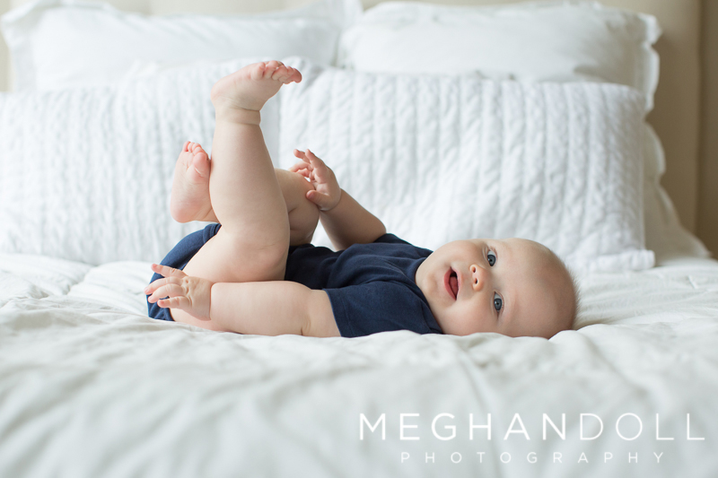 six-month-old-boy-plays-wth-toes-on-white-bed