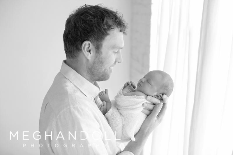 dad-holding-baby-near-window