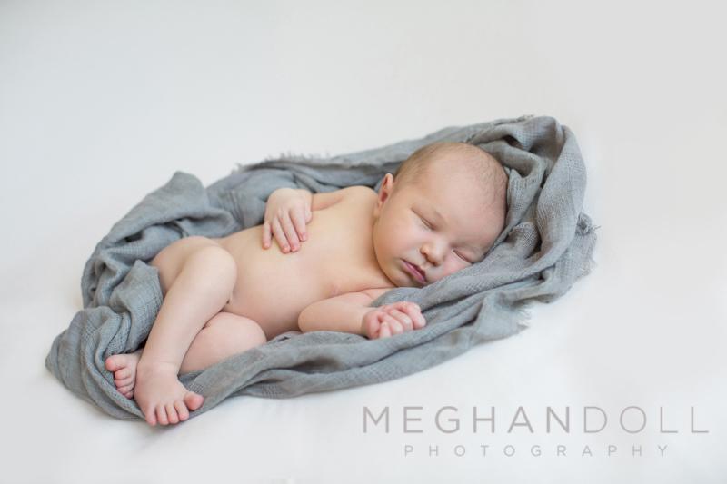 newborn-boy-laying-in-blue-wrap