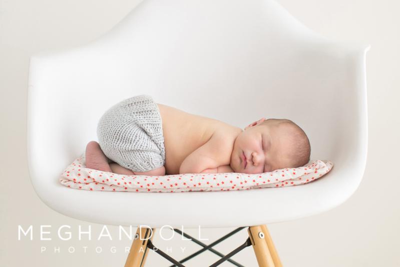newborn-laying-in-whit-chair-sleeping